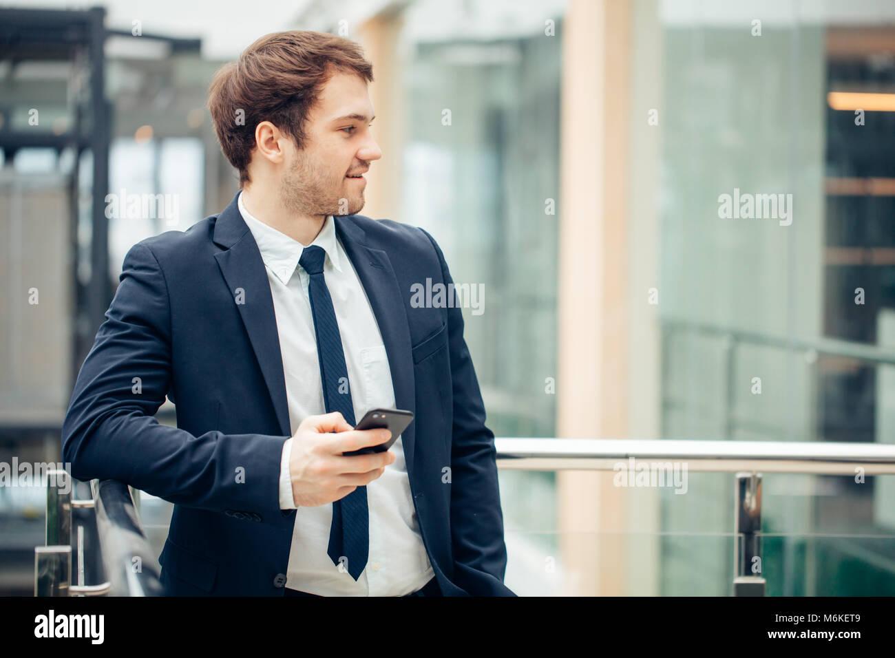 Geschäftsmann mit Smartphone über Bürogebäude Stockbild