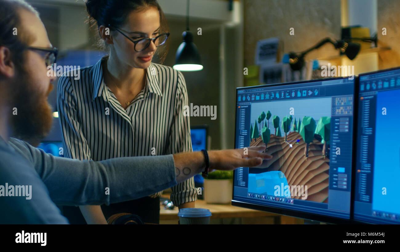 Männliche Game Developer Gespräche mit Künstlerischen weiblichen Level Designer. Zwei Displays zeigen Stockbild