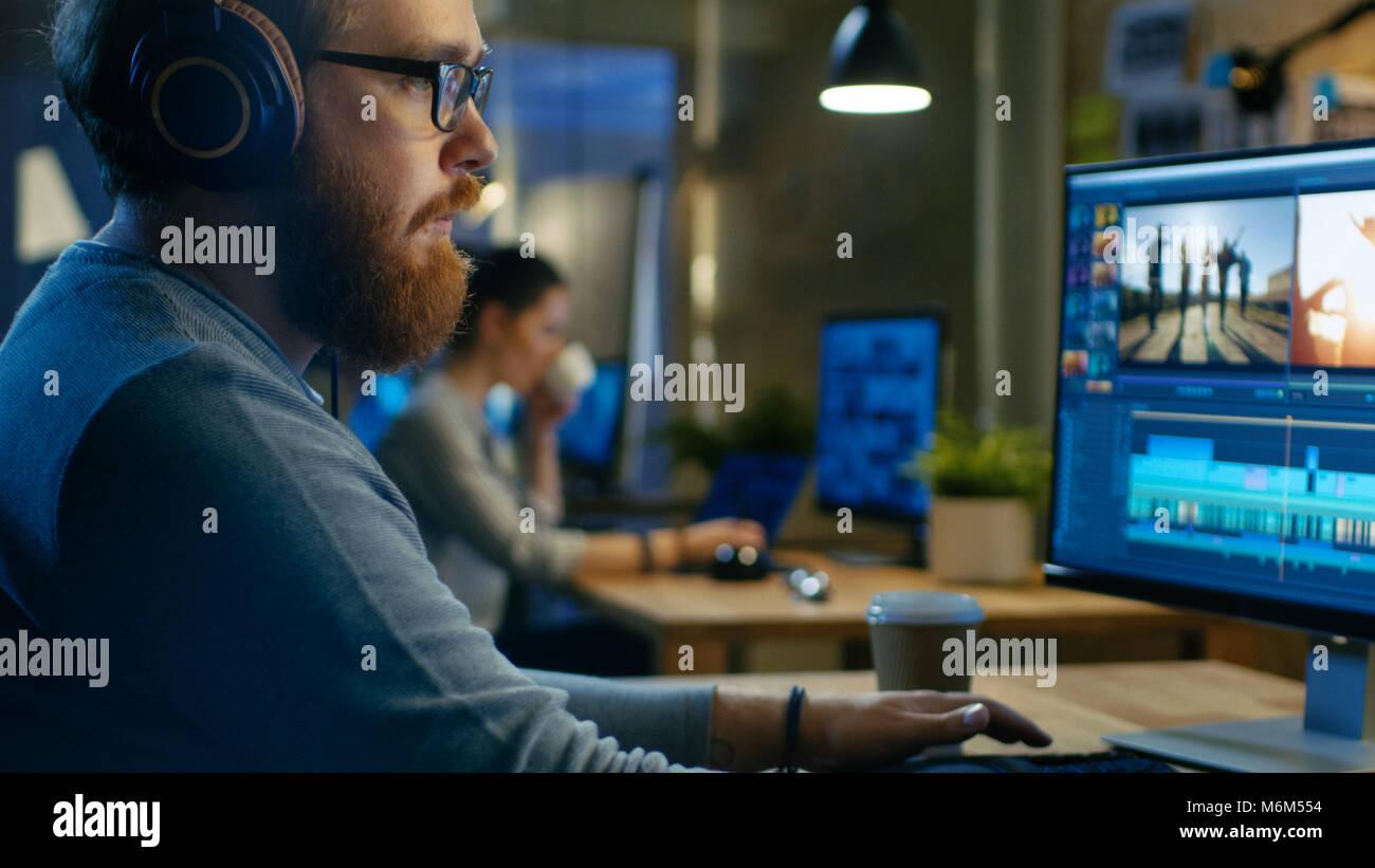 Männliche Videographer Bearbeitungen und Kürzungen Filmmaterial und Sound auf seinem Computer, setzt auf Stockbild