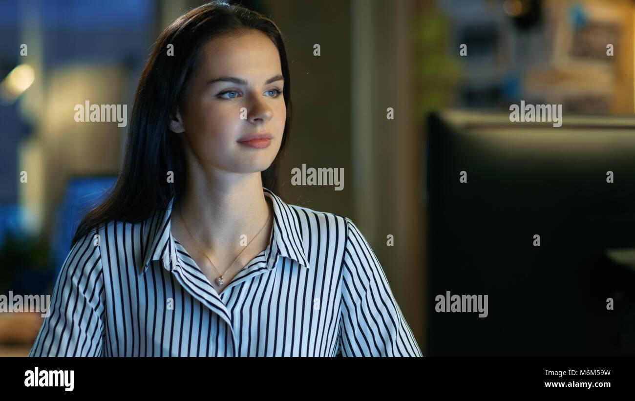 Schöne junge Frau arbeitet auf dem Computer. Sie arbeitet in einem modernen Büro Loft Studio Raum. Stockbild