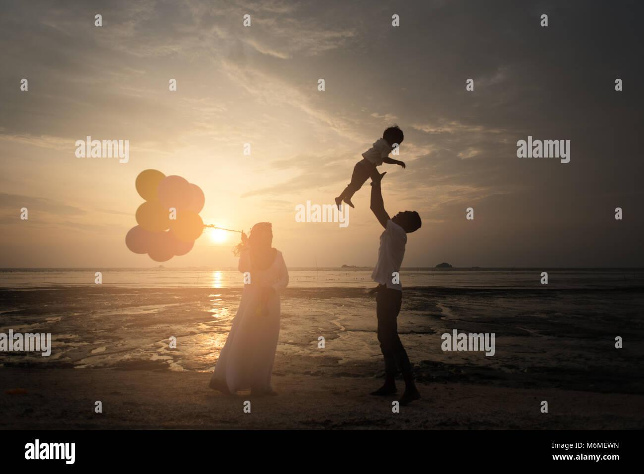 Sillhouette von glücklichen asiatischen Familie Spaß am Strand mit Blick auf den Sonnenuntergang als Hintergrund. Stockbild