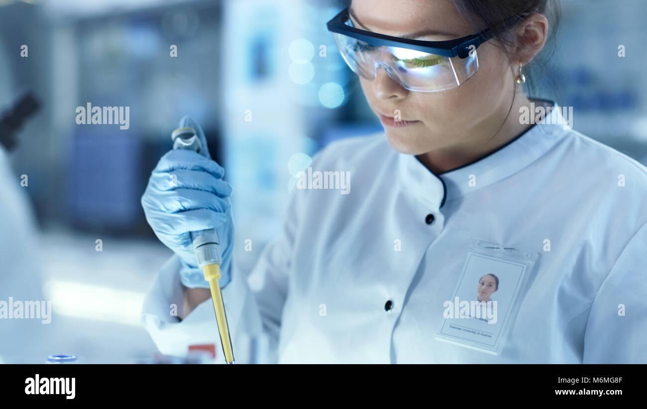 Weibliche Wissenschaftler verwendet Mikropipette Füllung Röhrchen in einem großen modernen Labor. Stockbild
