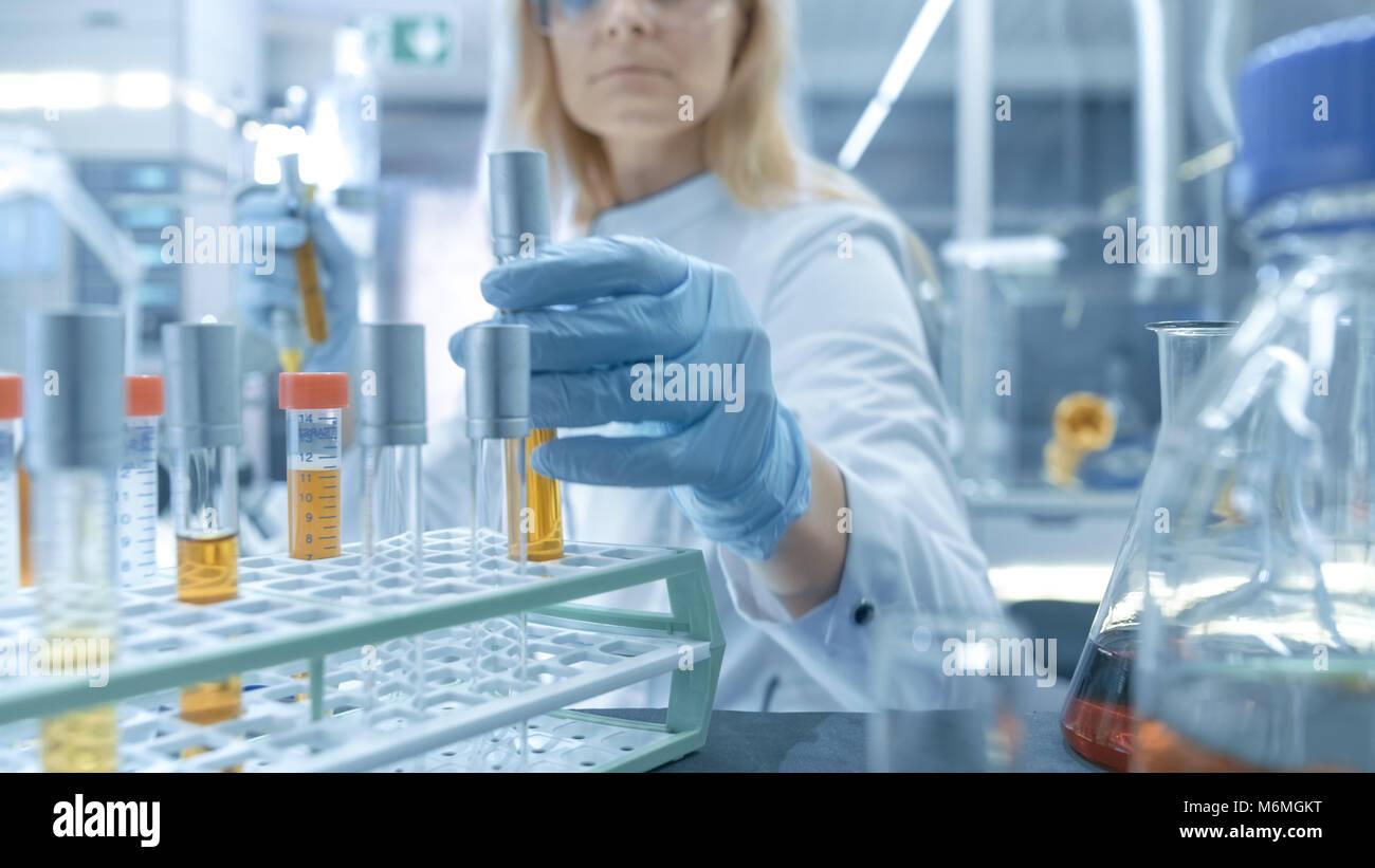 Medizinische Virologie Wissenschaftler arbeitet in einem Gefahrgut-Anzug mit Maske, inspiziert Reagenzglas mit isolierten Stockbild