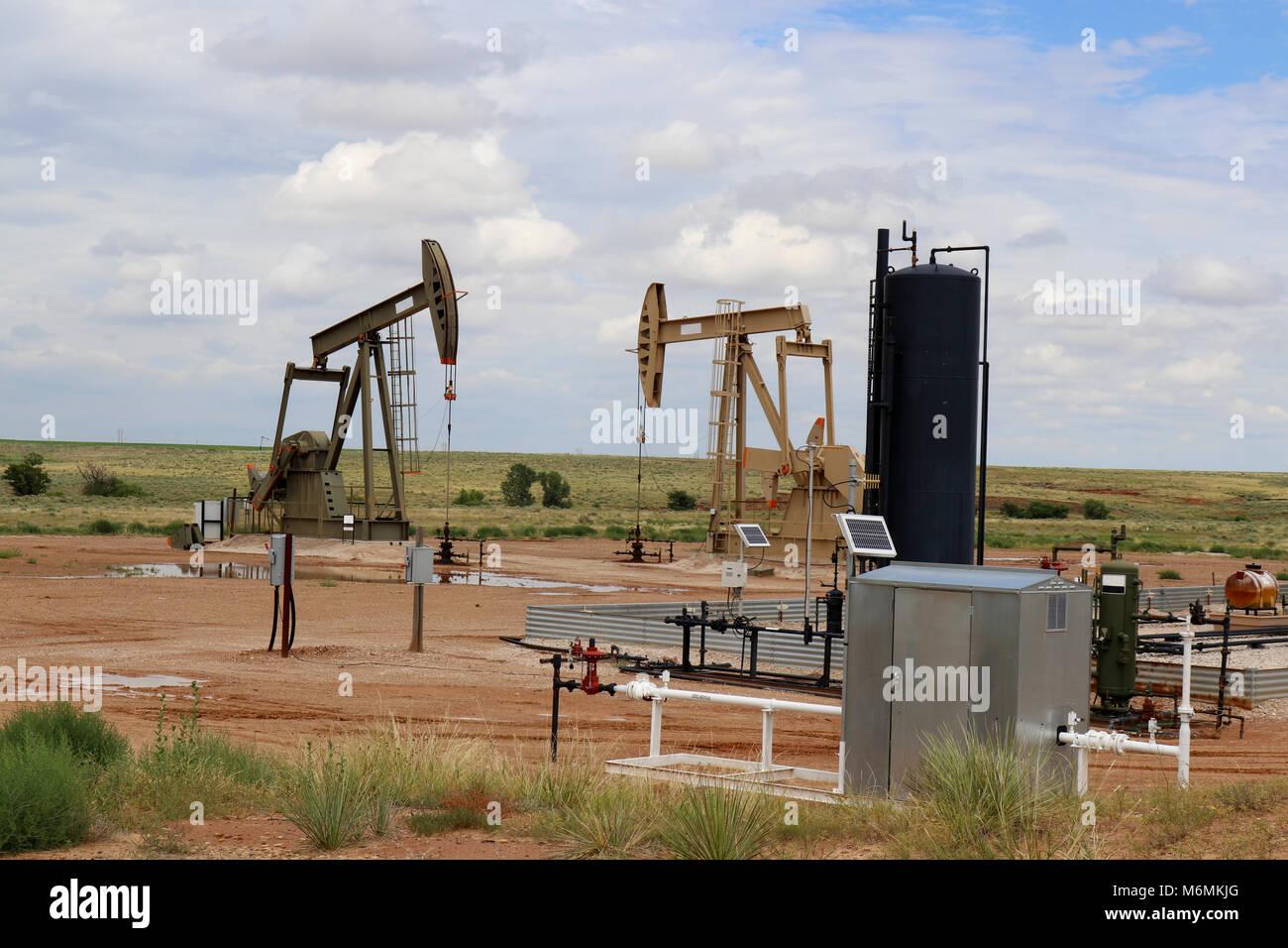 Zwei Öl - Gas und Jack Pumpe an der Bohrstelle mit Ausrüstung und Halten von Tanks auf praries mit niedrigen Hügel Stockfoto