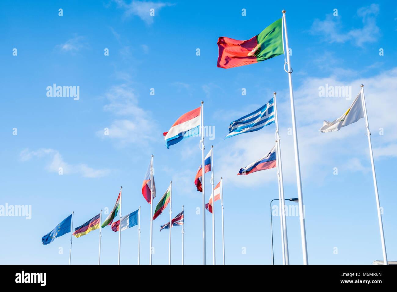 Viele Fahnen der verschiedenen Nationen der EU (Europäische Union) fliegen in den Wind vor blauem Himmel Stockbild