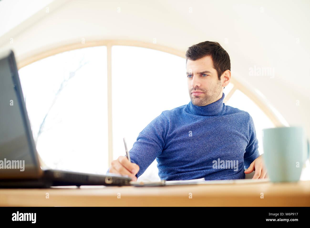 Portrait von Casual jungen Mann mit Rollkragen Pullover und Suchen thoughtul während auf Laptop zu Hause arbeiten. Stockbild