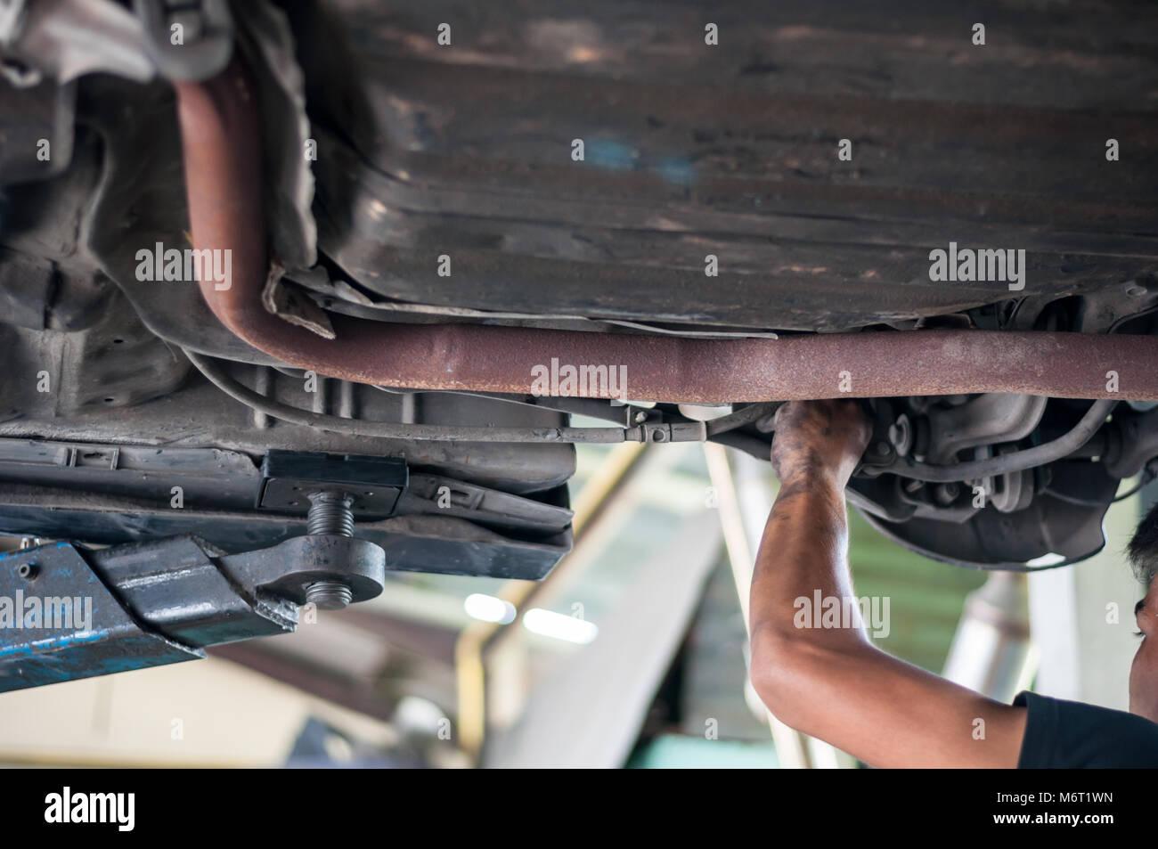 Automechaniker asiatischen Kontrolle bush-Schraube unter Doppelquerlenkerachse von Hand mit Tools Auto heben Stockbild