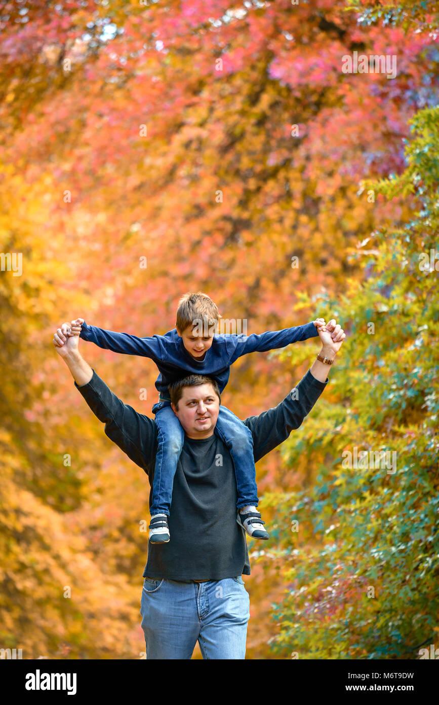 Vater Sohn piggyback Ride im Herbst Park Stockbild