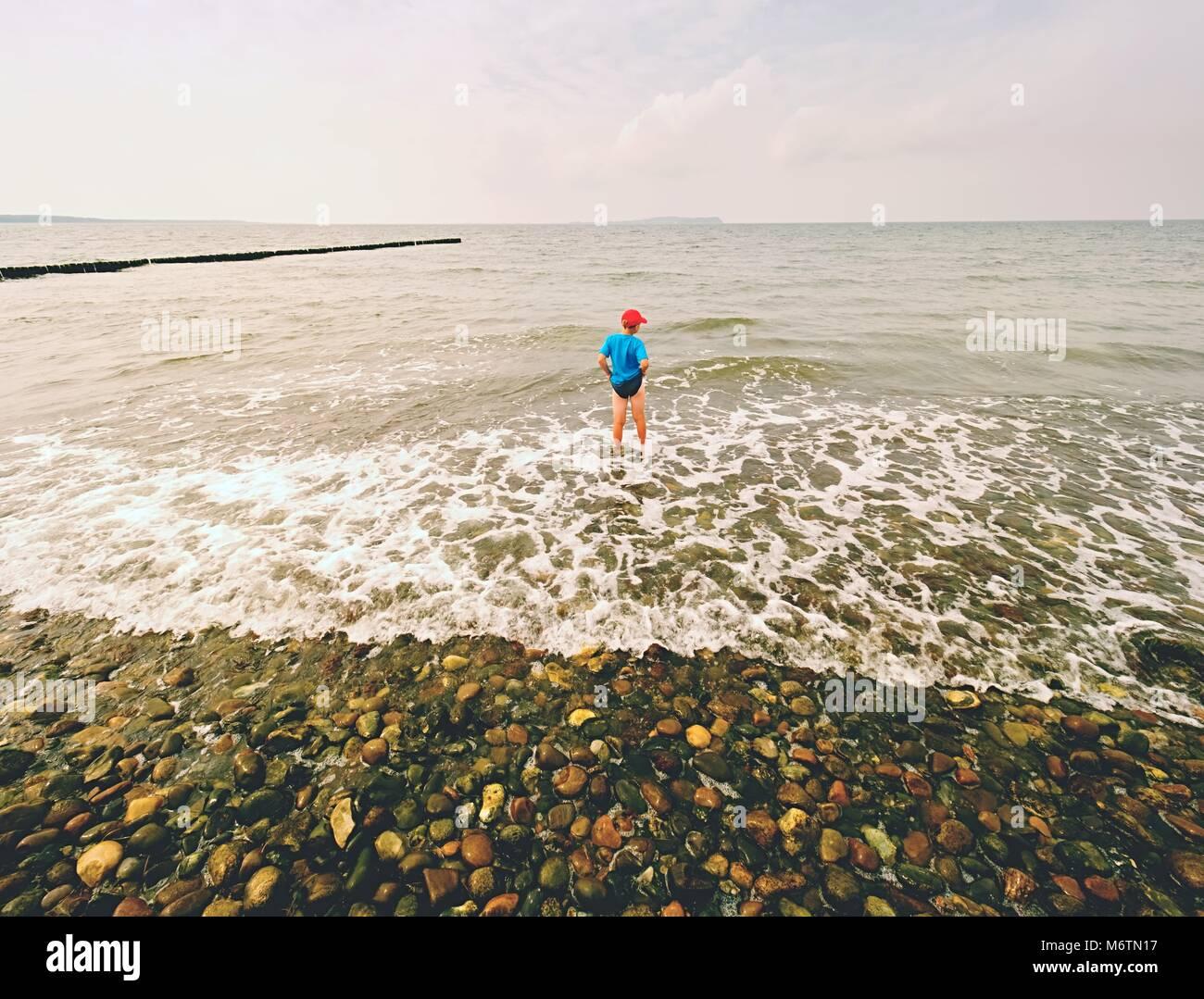 Junge in Blau Schwarz sportliche Kleidung Aufenthalt in kalten schäumende Meer. Blonde Haare Kind in Wellen Stockbild