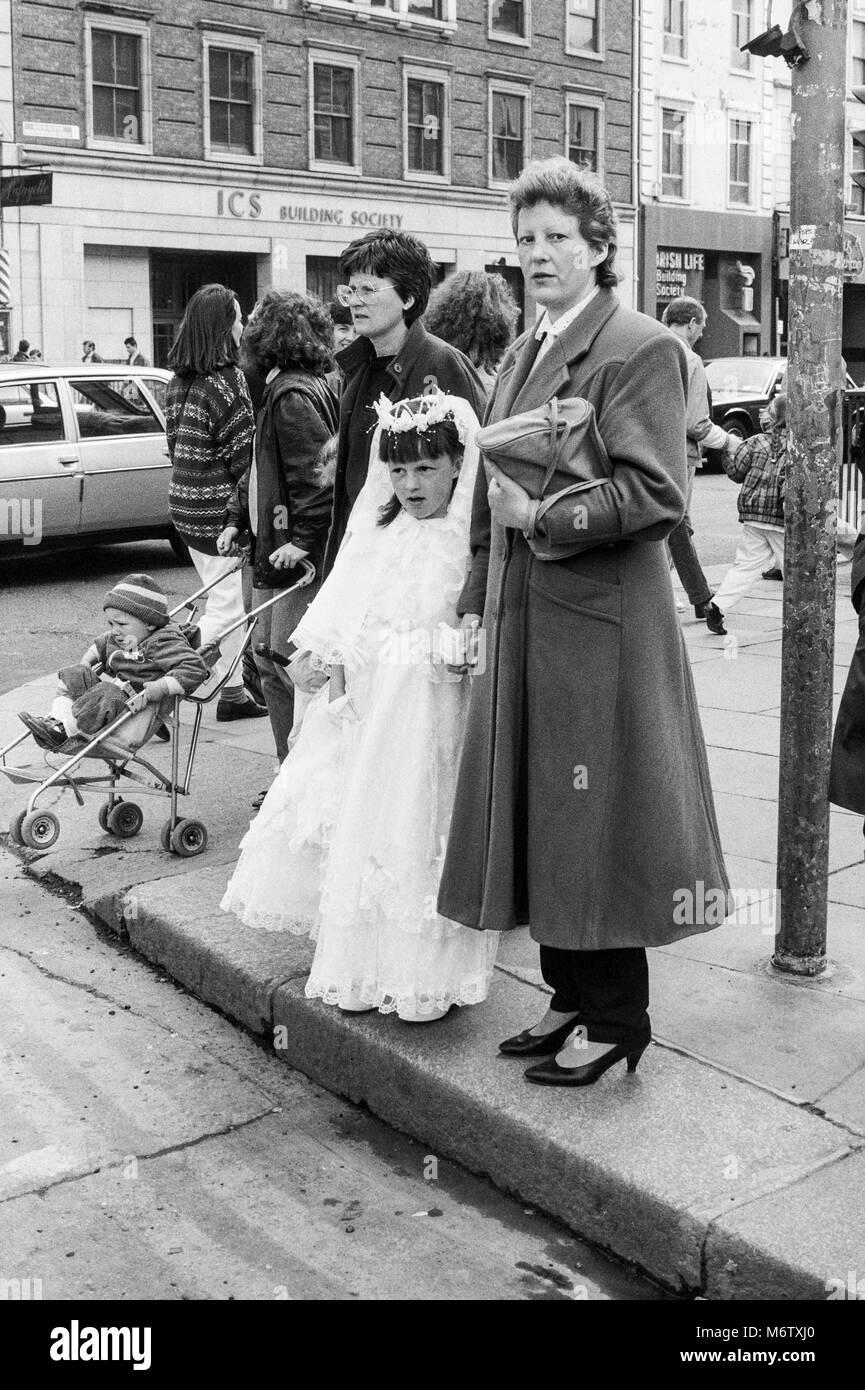 Junge Mädchen in der ersten Kommunion Kleid auf Straße Ecke warten, die Straße zu überqueren, Stockbild