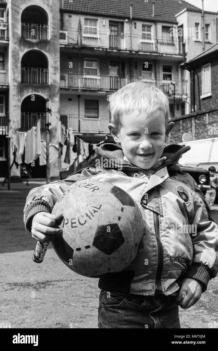 Junge mit Fußball im Hof eines Mietshauses Block im Stadtzentrum von Dublin, Irland, Archivierung Foto von Stockbild