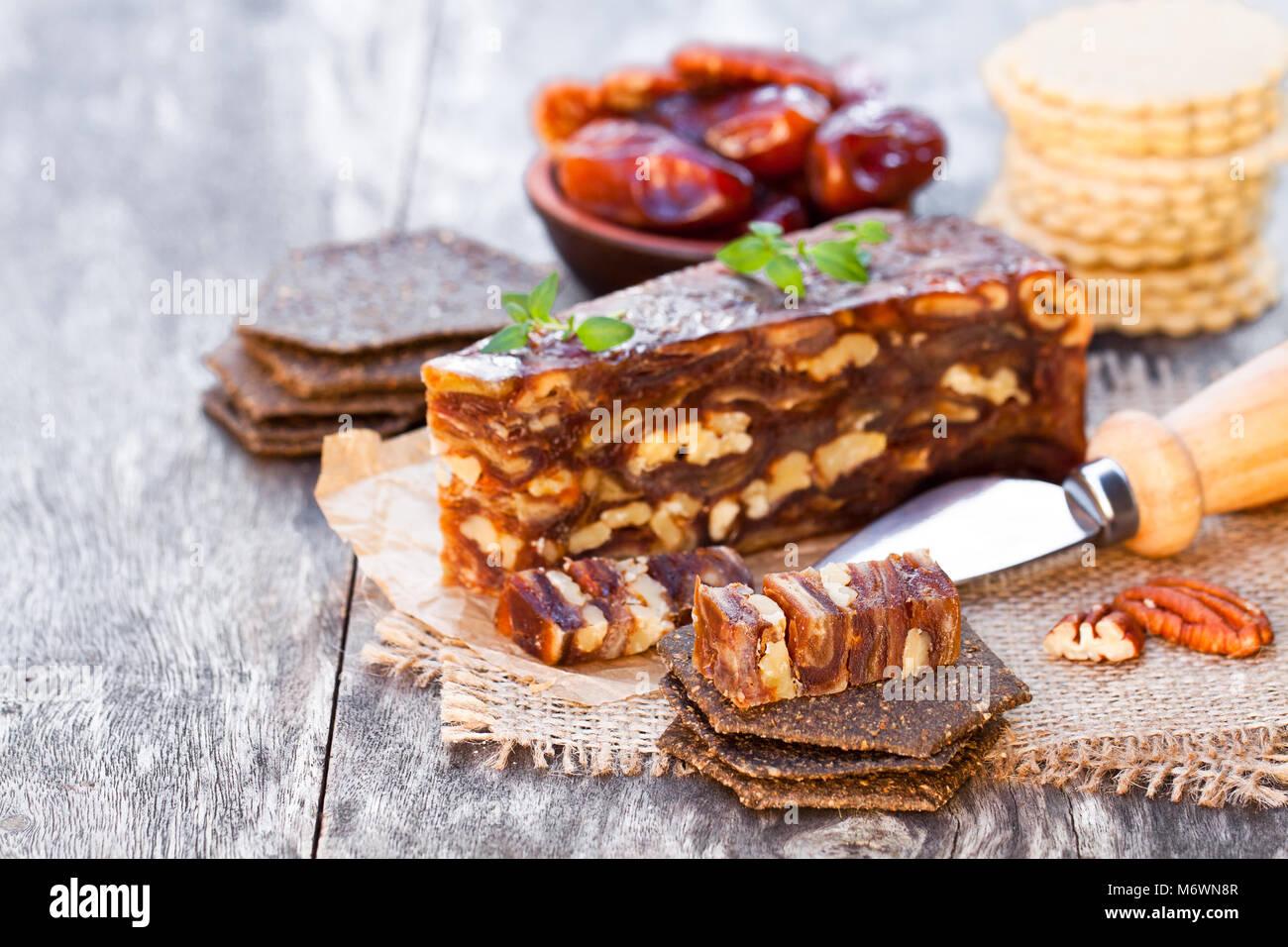 Datum Nussbaum Keil mit Mehrkorn Cracker auf hölzernen Tisch Stockbild