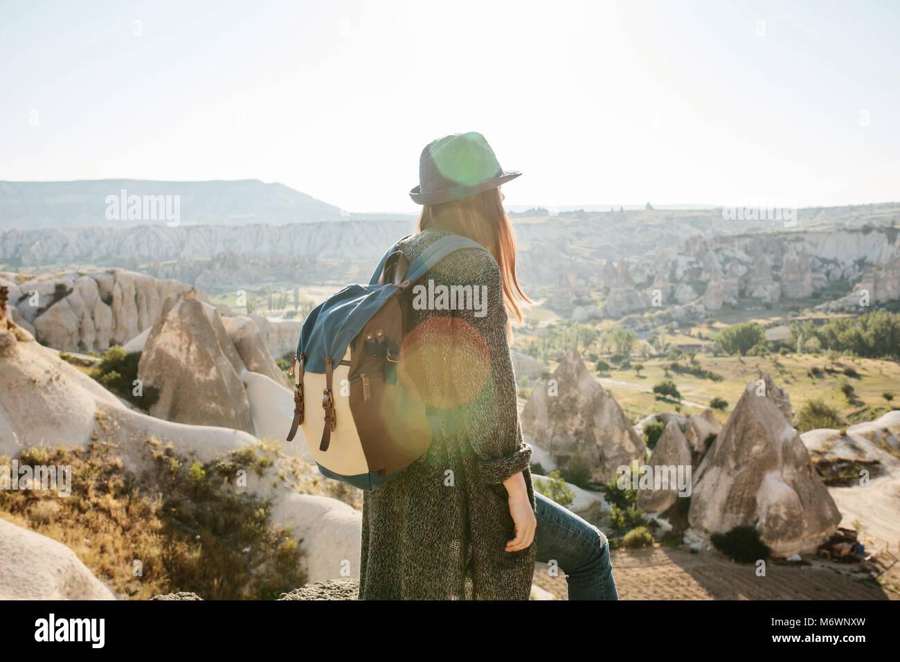 Ein Reisender in einen Hut mit einem Rucksack steht auf einem Berg und blickt auf einen wunderschönen Blick Stockbild