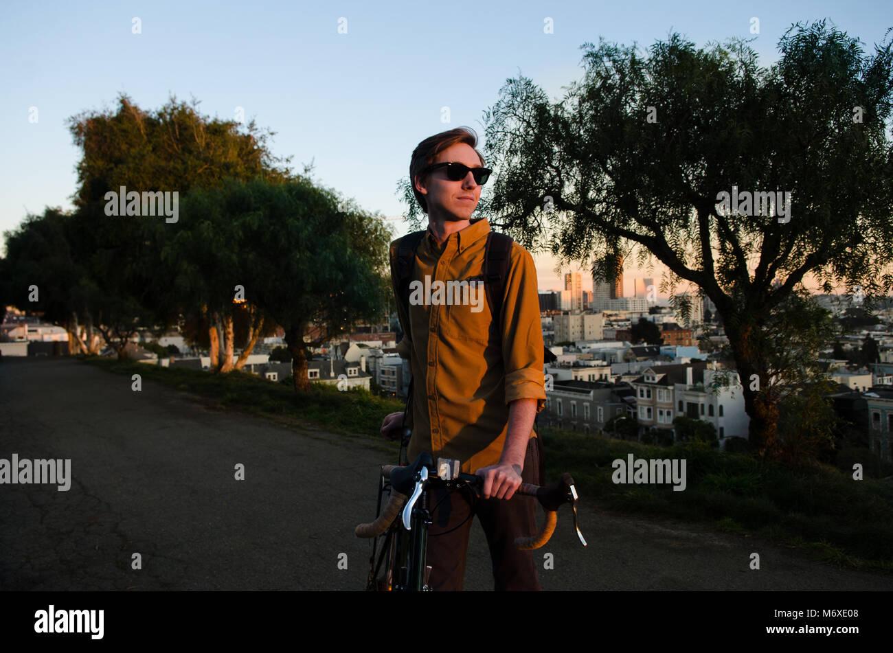 Mann sein Fahrrad in einem Park Stockbild