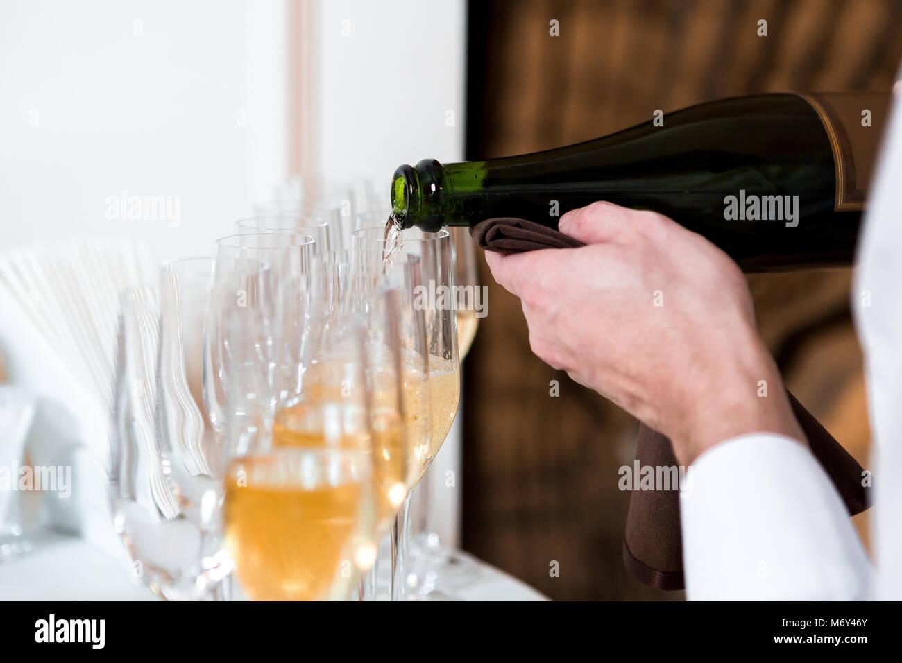 Kellner gießt Champagner Stockbild