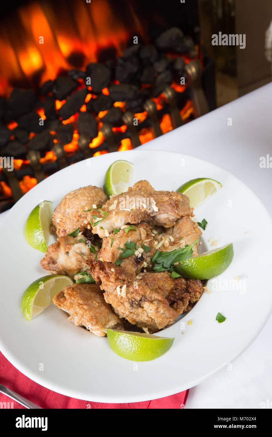Frango eine passarihno, ein brasilianisches Gericht der Fried Chicken Stücke in Kalk- und Knoblauch mit Kalk Stockbild