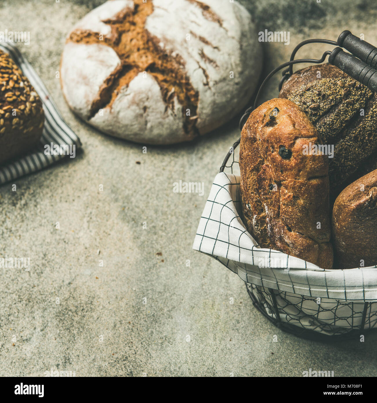 Verschiedene Brot Brote auf grauem Beton Hintergrund, Quadrat Erntegut Stockbild