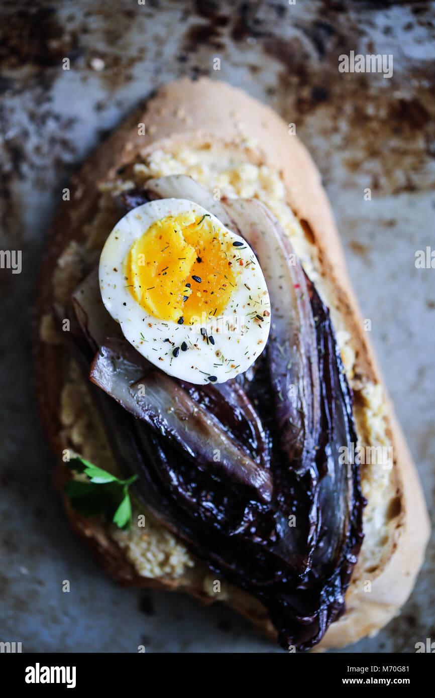 Geschmorte rote Chicorée Crostini mit Hummus, gekochtem Ei und Gewürze Stockbild