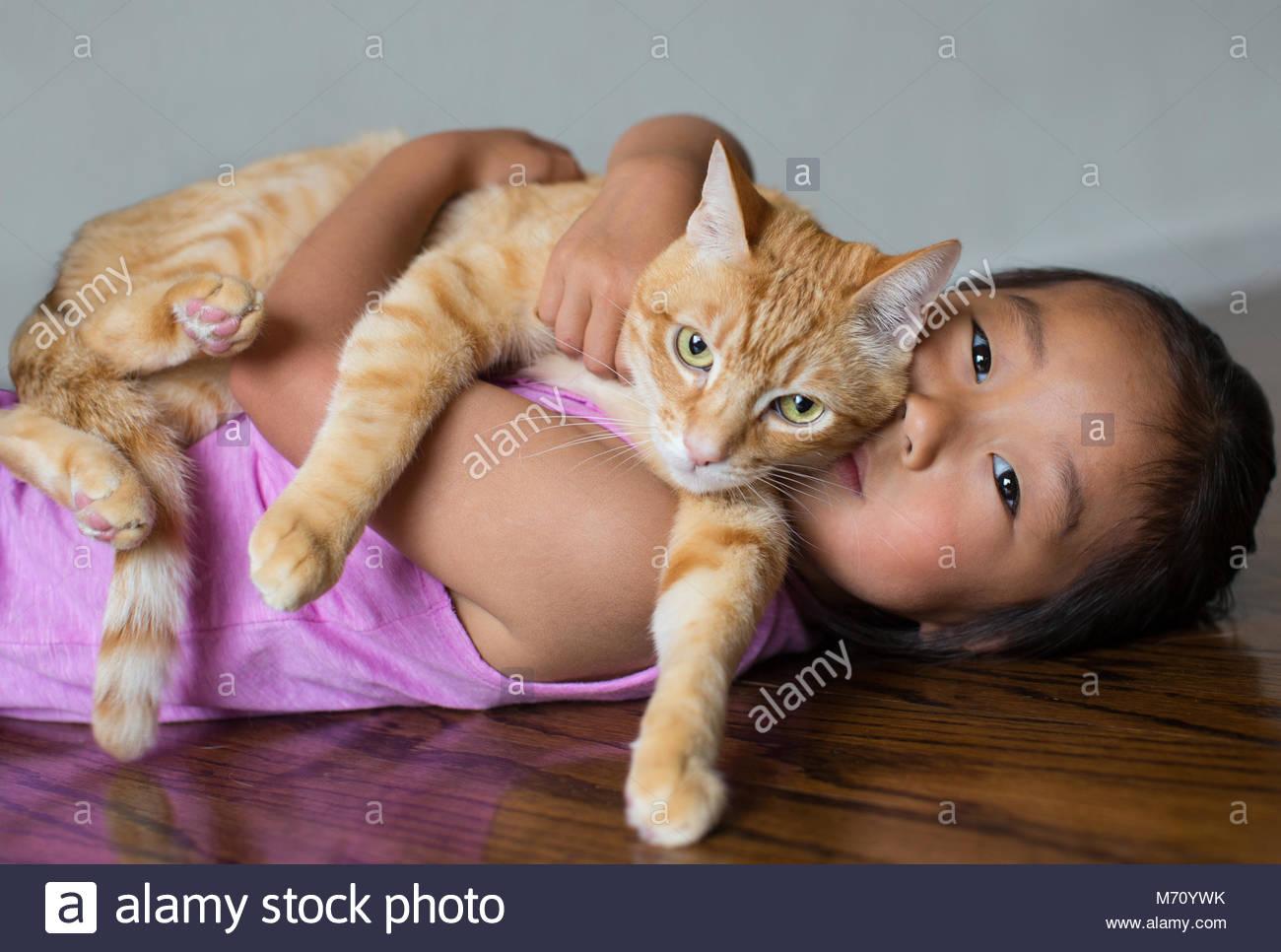 Junge asiatische Mädchen liegt auf Holz Stock Holding eine orange tabby Katze auf ihre Brust und Suchen in Stockbild