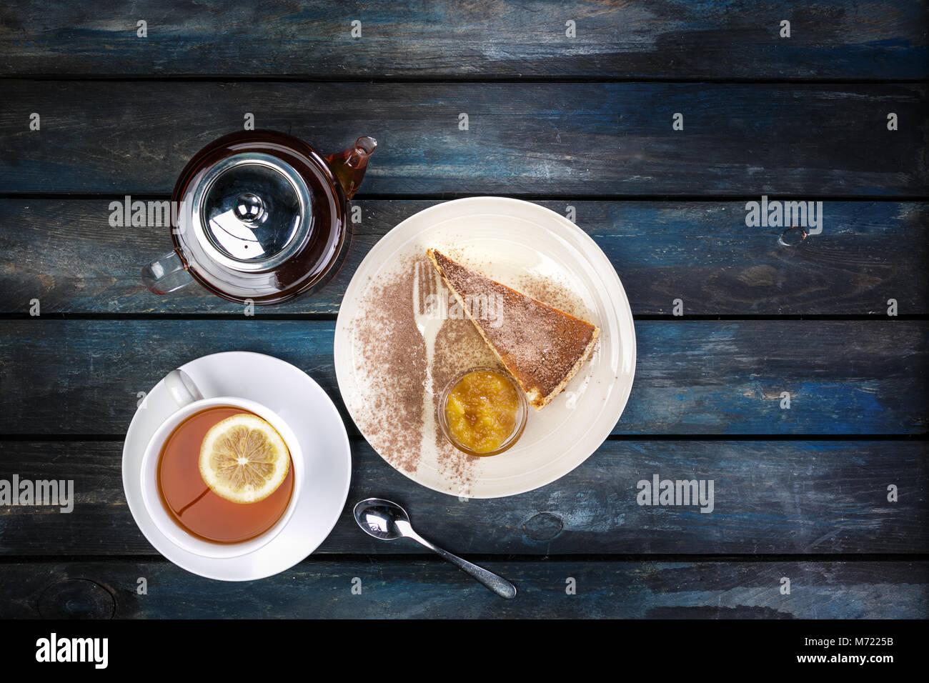 Stück Käsekuchen mit Marmelade und Tee Wasserkocher mit Zitrone auf einem farbigen Hintergrund aus Holz. Stockbild