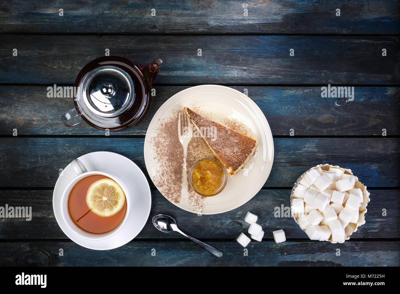 Stück Käsekuchen mit Marmelade und Tee Wasserkocher mit Zitrone und rafinated Zucker auf einem farbigen Stockbild