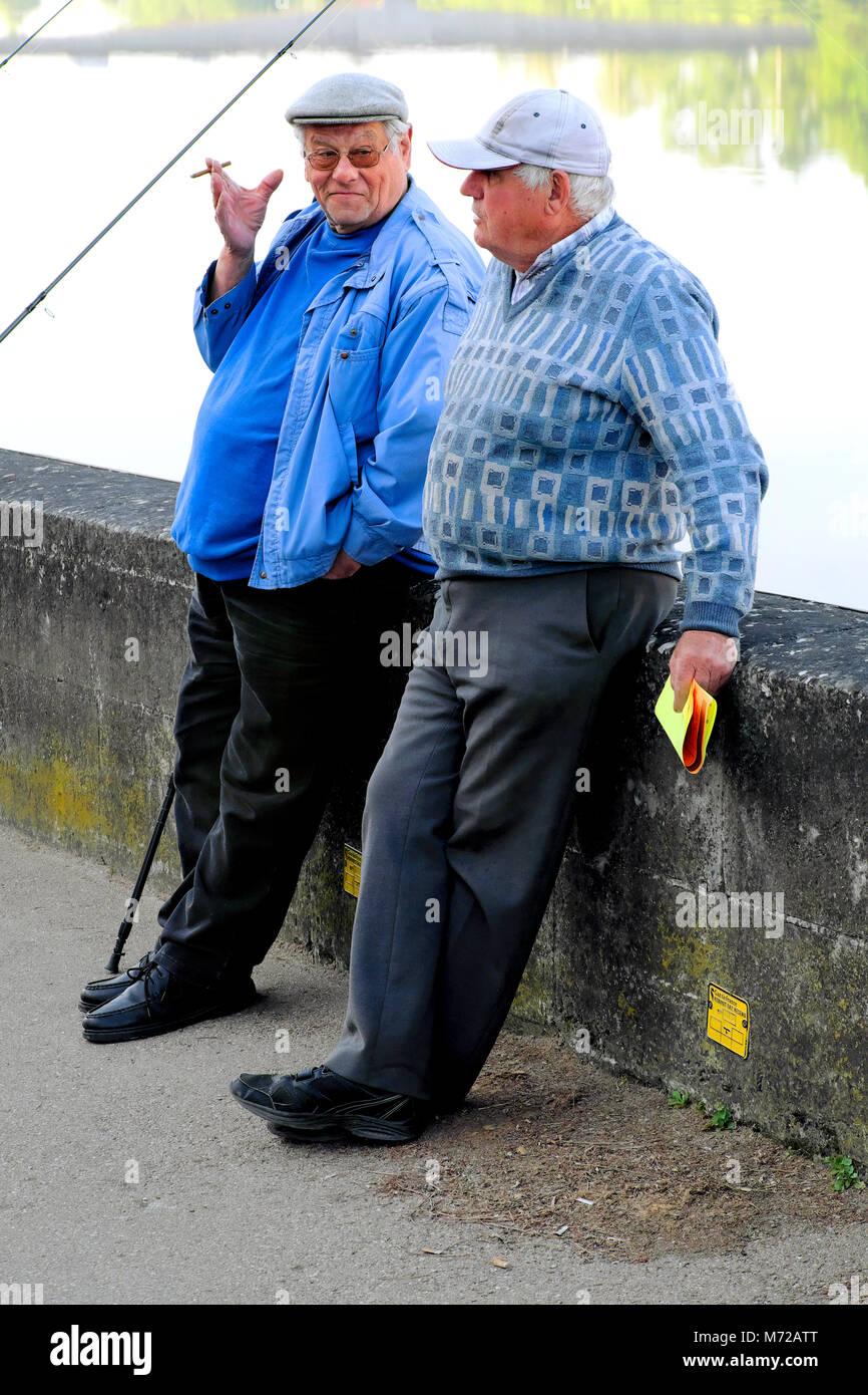 Zwei ältere Männer rauchen und Reden während der Pause vom Angeln im Fluss Dordogne, Bergerac, Nouvelle-Aquitaine, Stockfoto