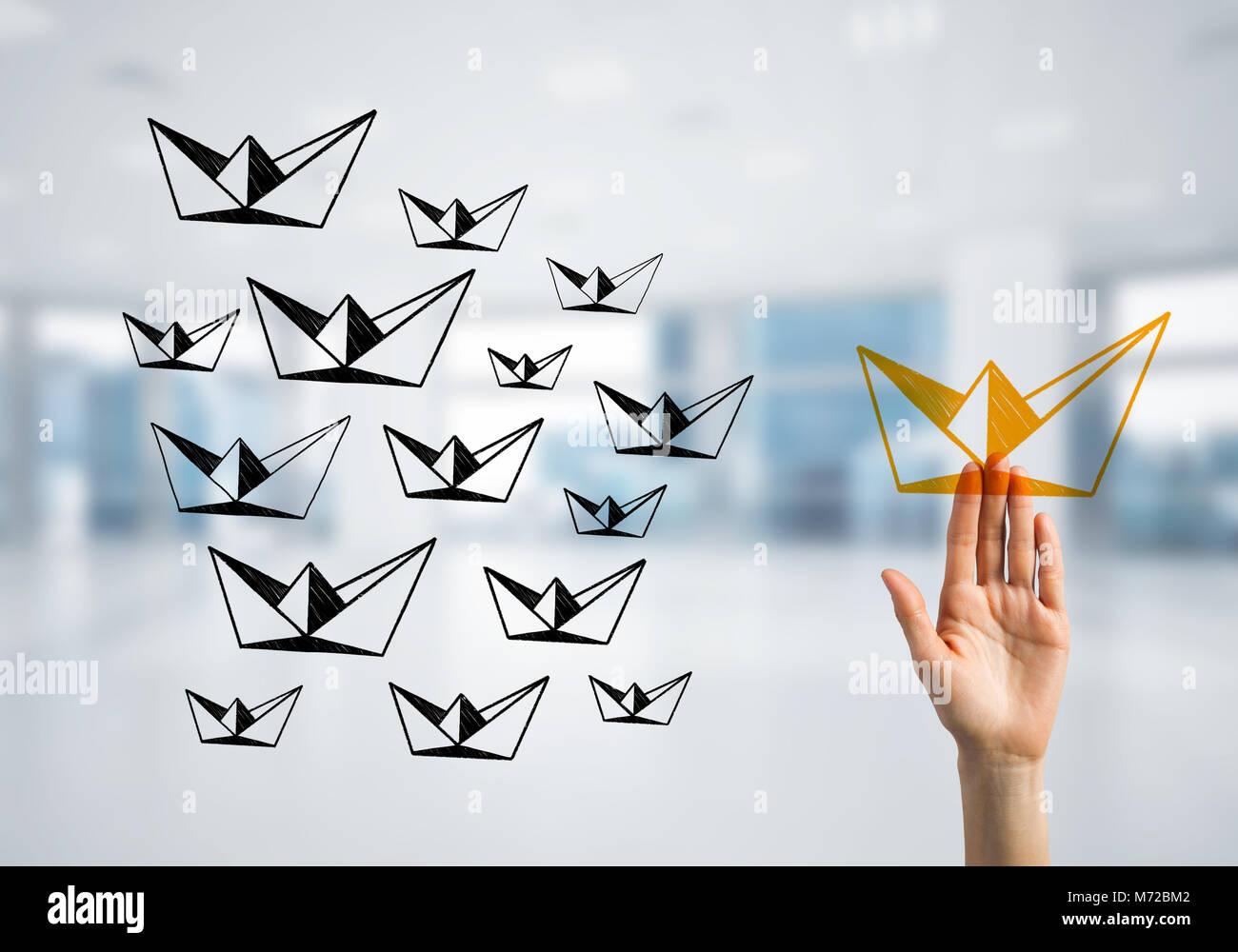 Konzept der Führung und Teamarbeit mit vielen Symbolen und einer von ihnen abheben Stockbild