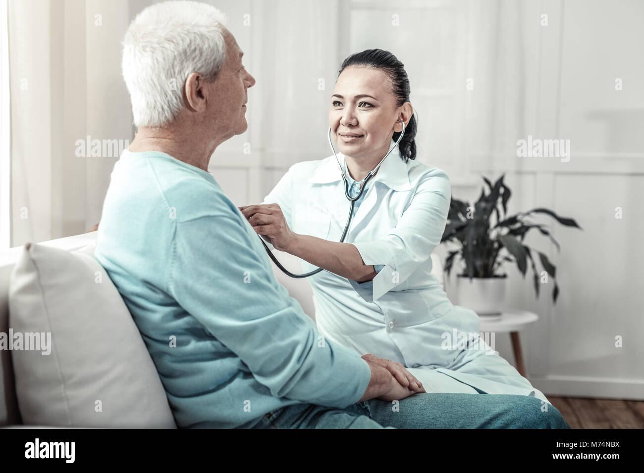 Junge qualifizierte Krankenschwester sitzen und lauschen Sie dem Patienten Lunge. Stockbild