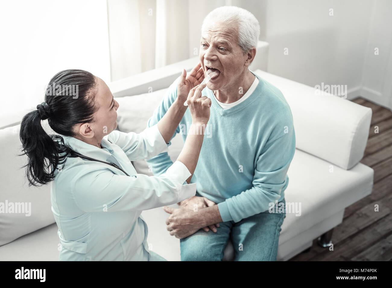 Alte ernster Mann an der Krankenschwester seine Zunge angezeigt. Stockbild