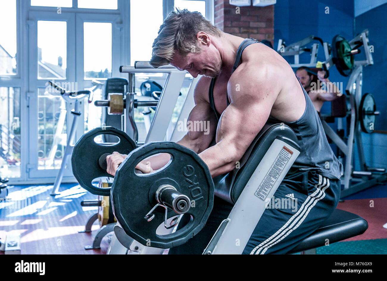 Muskulöse Mann, Arbeit mit Gewichten in der Turnhalle Stockbild