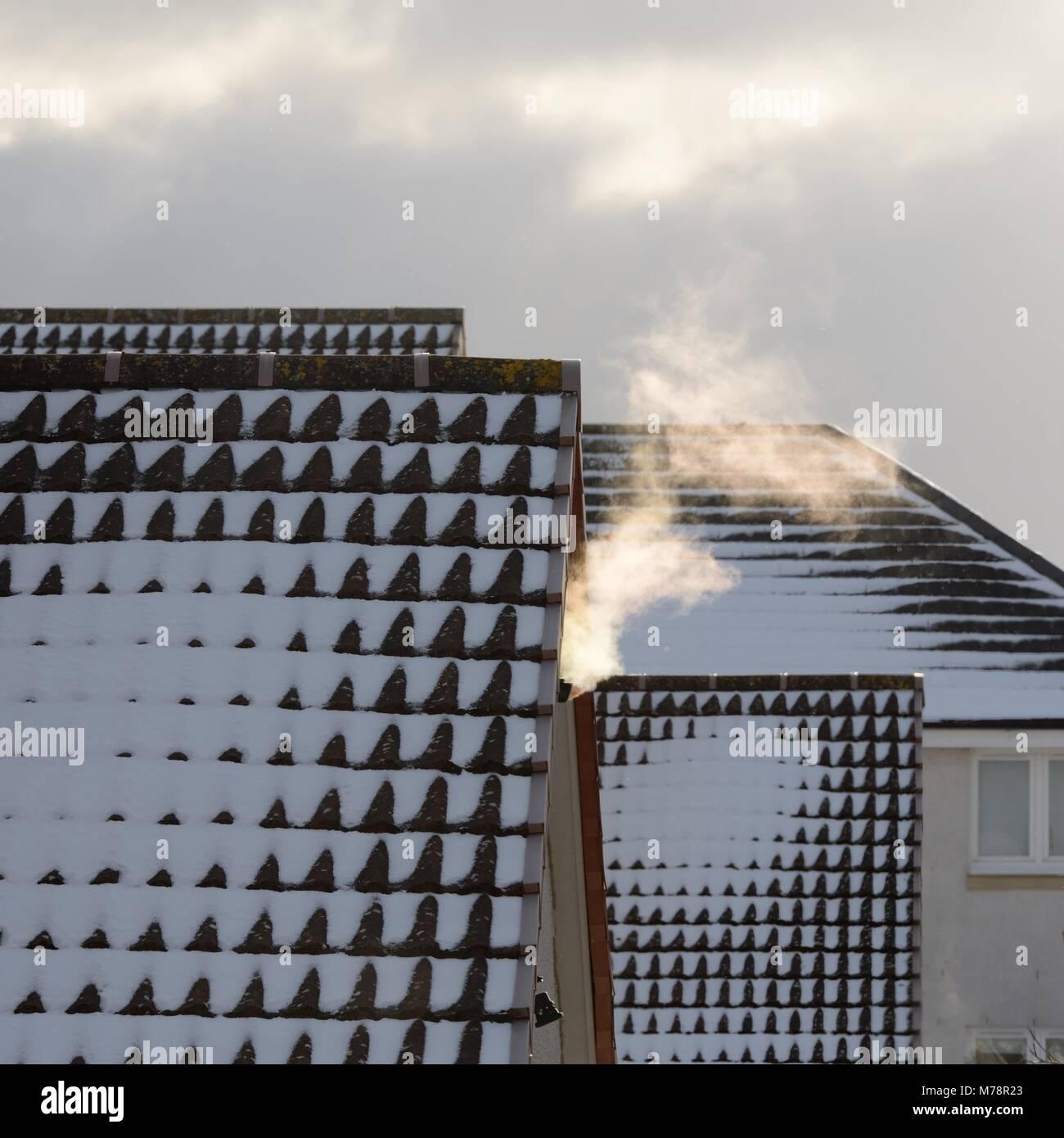 Aus einer Heizung Dampf treibt Vent über die Dächer im Schnee bei kaltem Wetter in Schottland, UK abgedeckt Stockbild