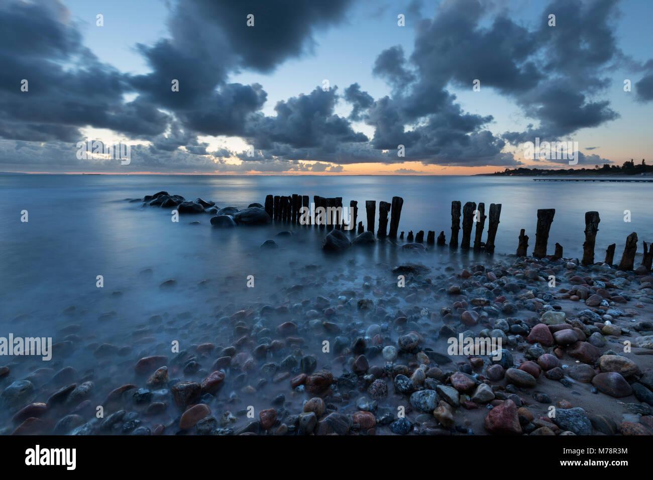 Alten hölzernen Pfähle aus auf das Meer und die Kieselsteine am Strand bei Sonnenaufgang, Munkerup, Kattegat Coast, Stockfoto