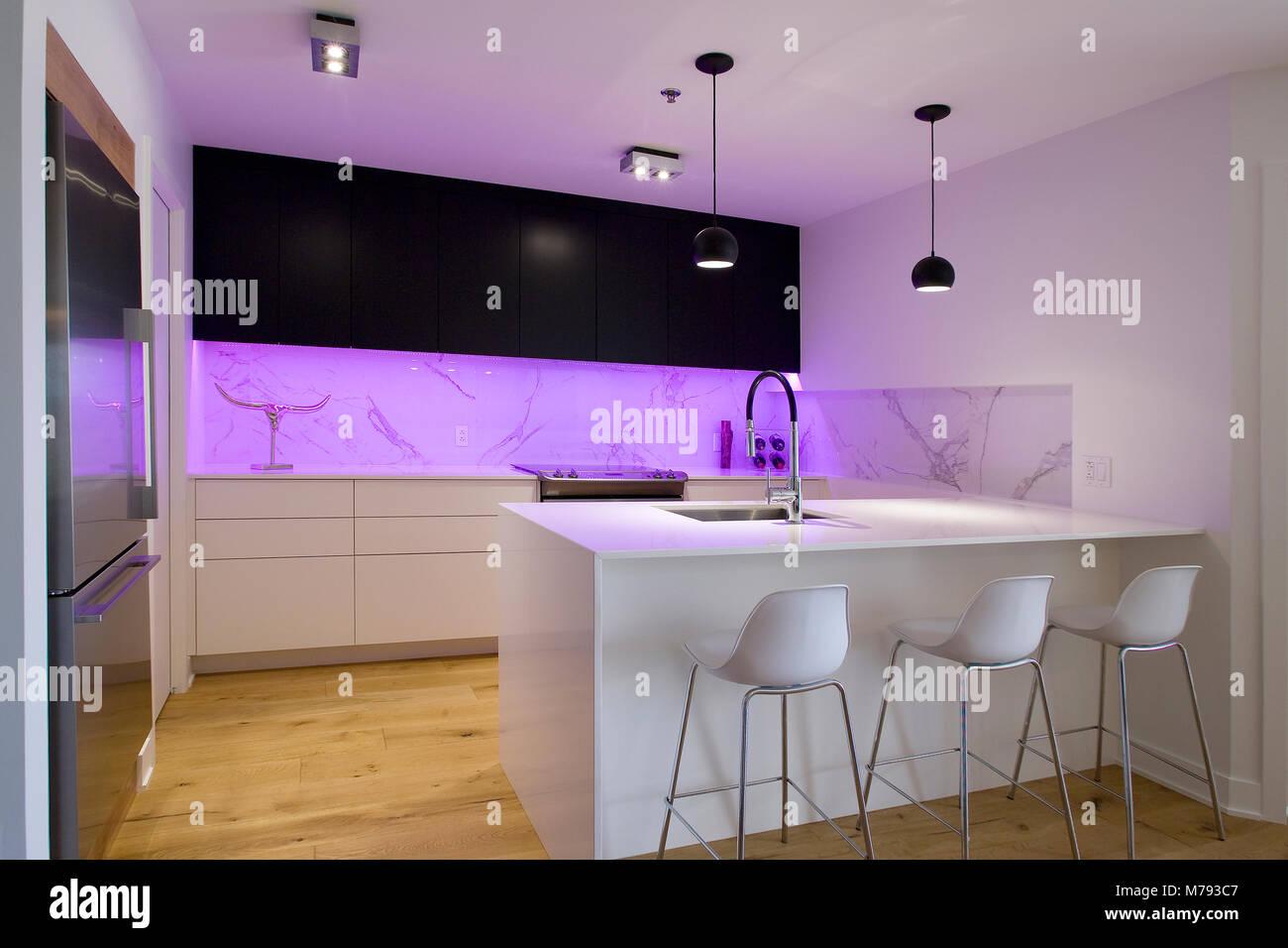 Schwarze und weiße Küche mit Insel und Hocker und ein violetter ...