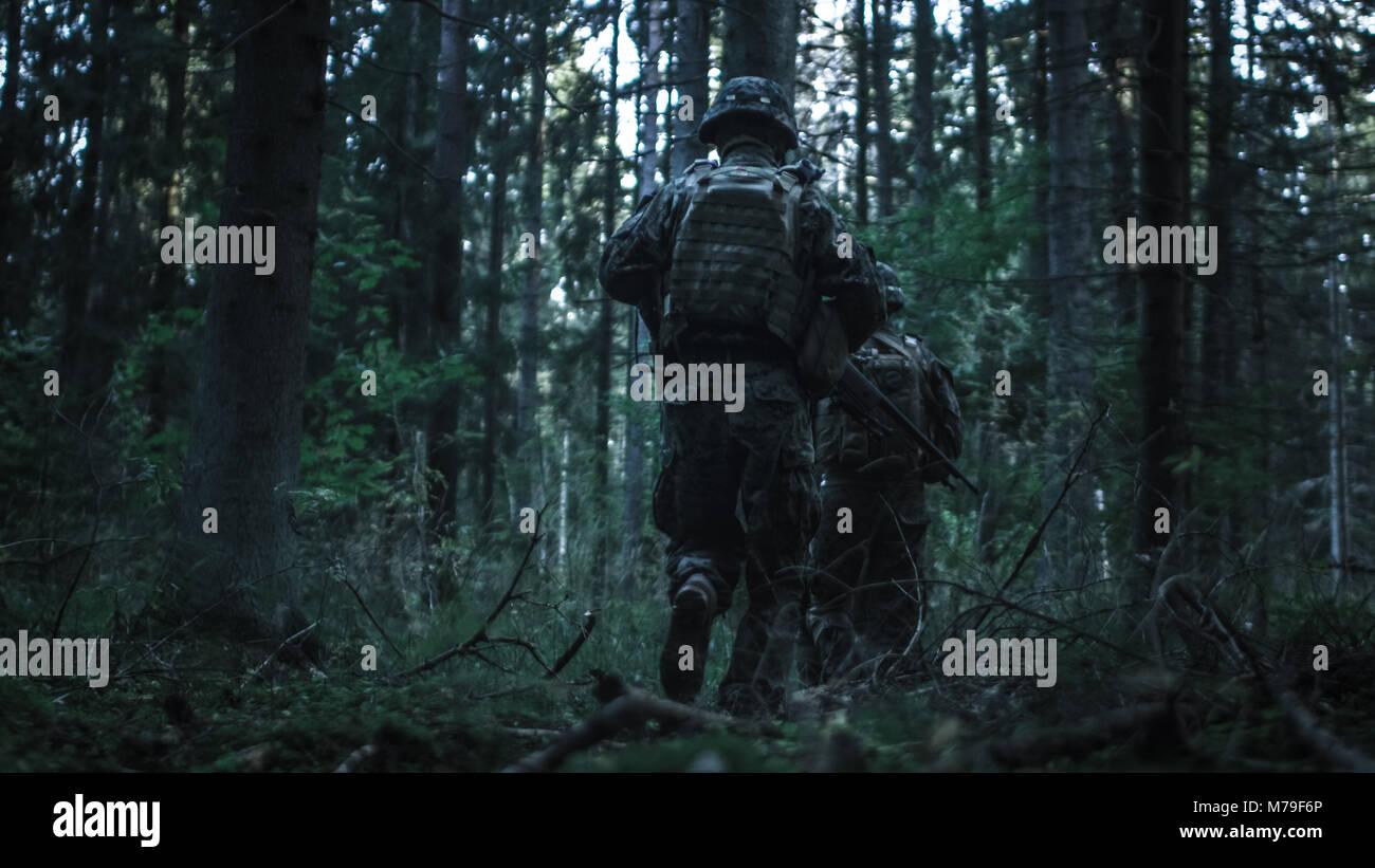 Voll ausgestattete Soldaten Gruppe fährt weiter in den dichten Wald. Sie bereitgestellt auf der Aufklärer Stockbild