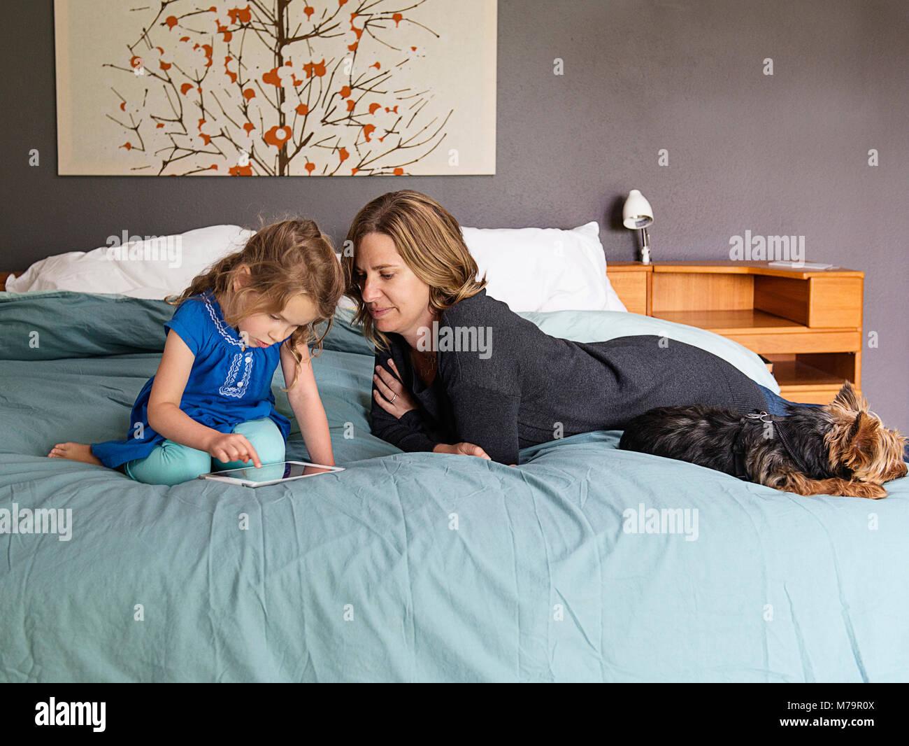 Eine Frau, die ihre Tochter Beobachten lernen, wie man mit einem ipad mini schreiben. Stockbild