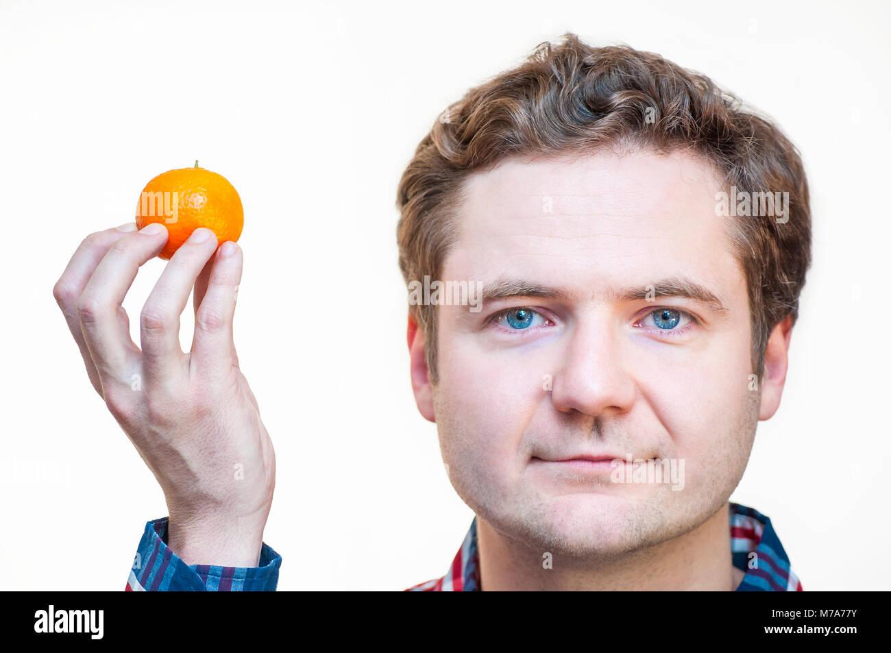 Porträt der jungen blauäugigen kaukasischen Ethnie Mann, Tangerine in der Rechten in der Nähe seinen Stockbild