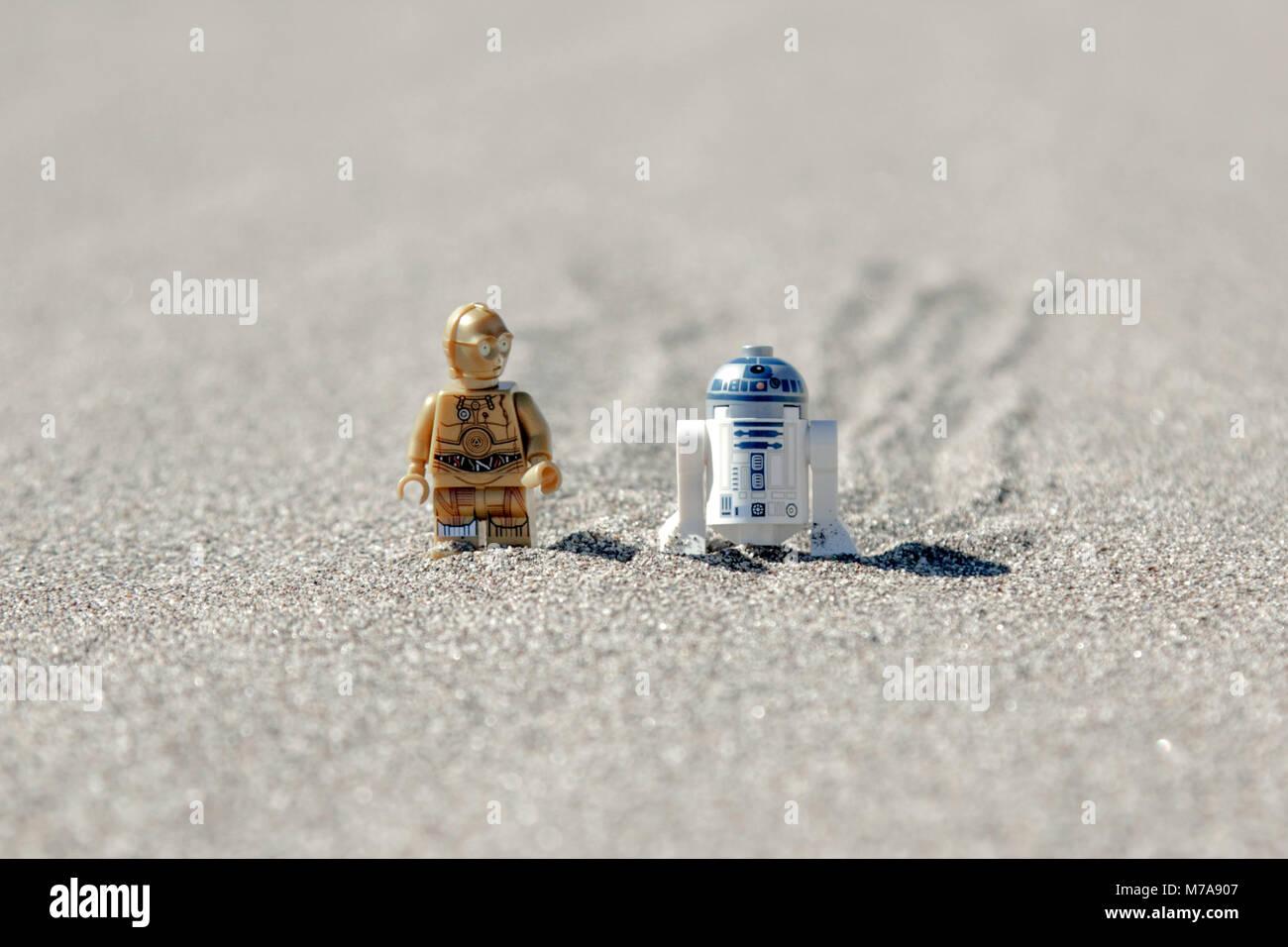 Lego C3p 0 und Lego R2D2 zu Fuß durch eine Sanddüne zusammen. Stockbild