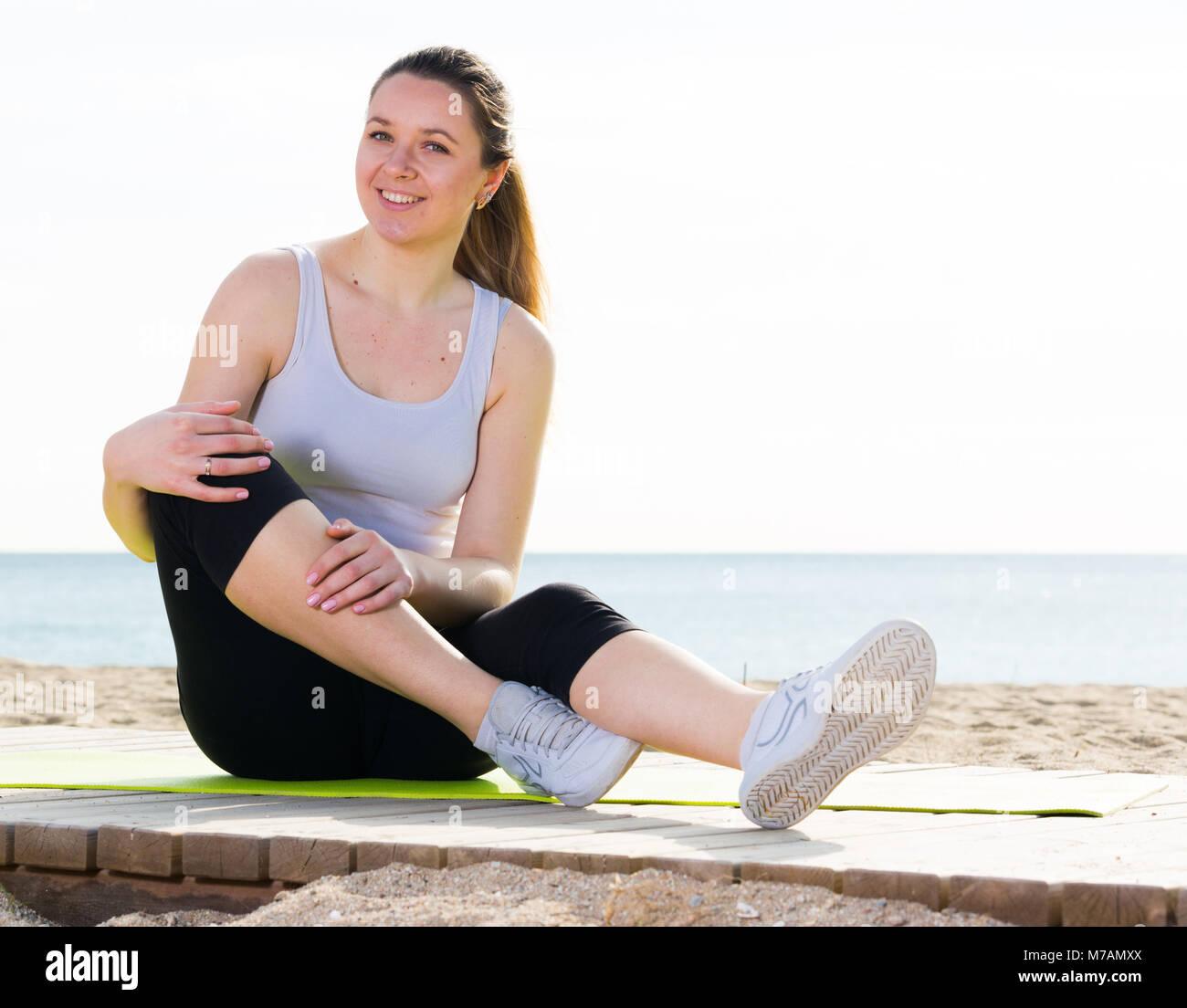Lächelnde Mädchen mit verschiedenen Posen während der regulären Training am Strand Stockbild