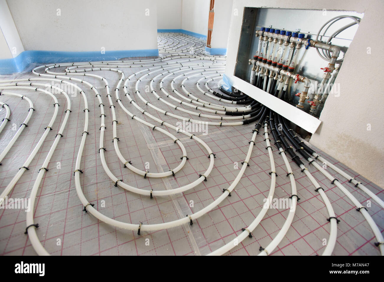 Hausbau mit Innenausbau der Fußbodenheizung und Abwasserentsorgung Stockbild