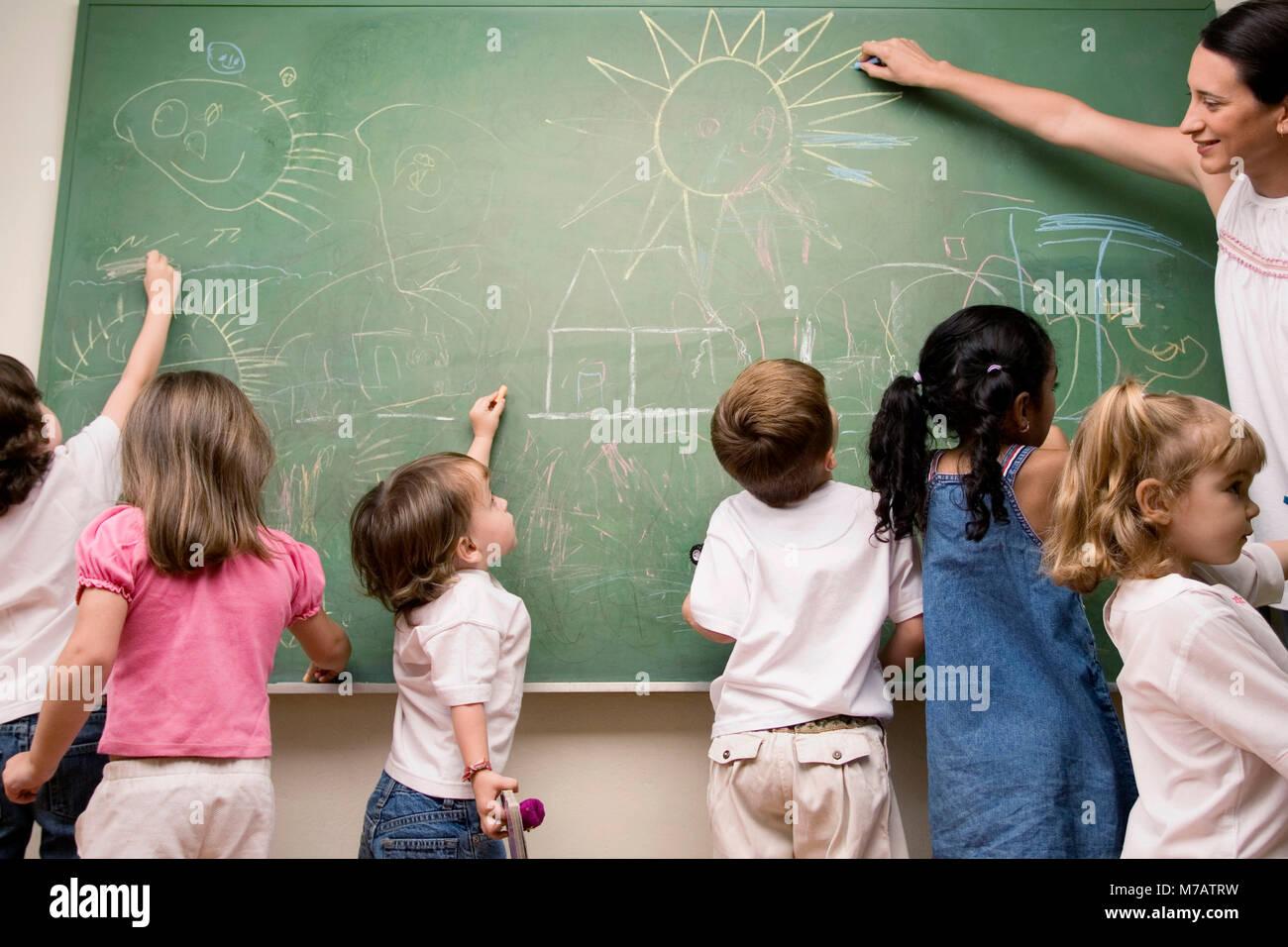Weibliche Lehrer unterrichten ihre Schüler in einem Klassenzimmer Stockbild 2859e348d4