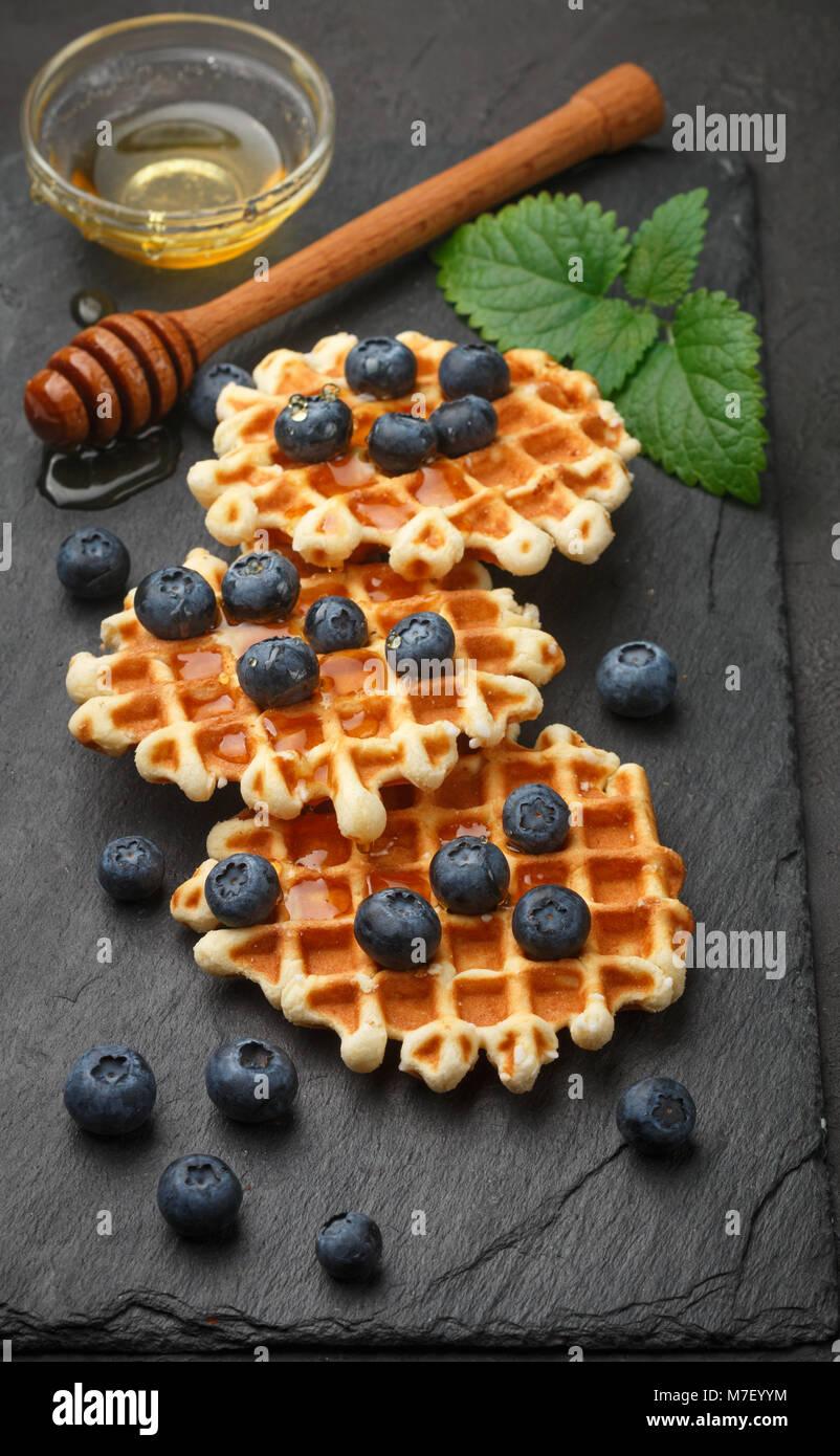 Wiener Waffeln mit Honig und frischen Beeren Heidelbeeren und Minze auf schwarzen Oberfläche. Köstliches Stockbild