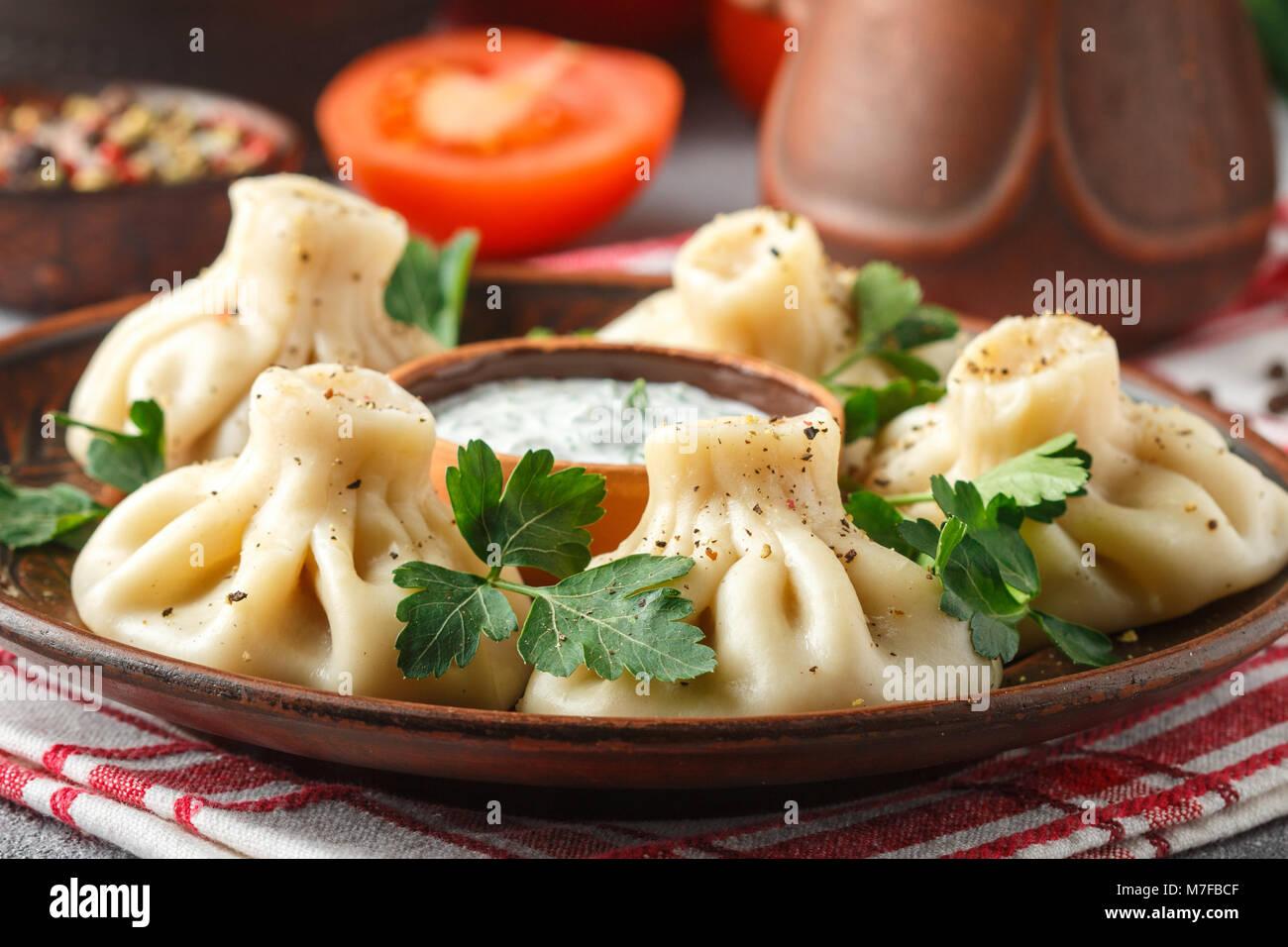Khinkali - Georgische Knödel mit Fleisch und Petersilie in eine keramische Schüssel mit einer Sauce aus Stockbild