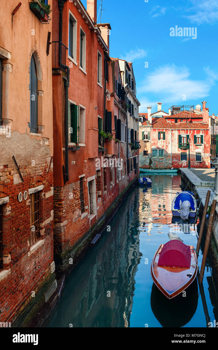 Boote auf dem schmalen Kanal entlang alter Backsteinhäuser in Venedig, Italien (vertikale Komposition). Stockbild