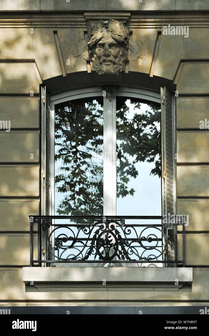 Eines der Fenster in Paris auf dem Hintergrund einer beige Wand mit ...