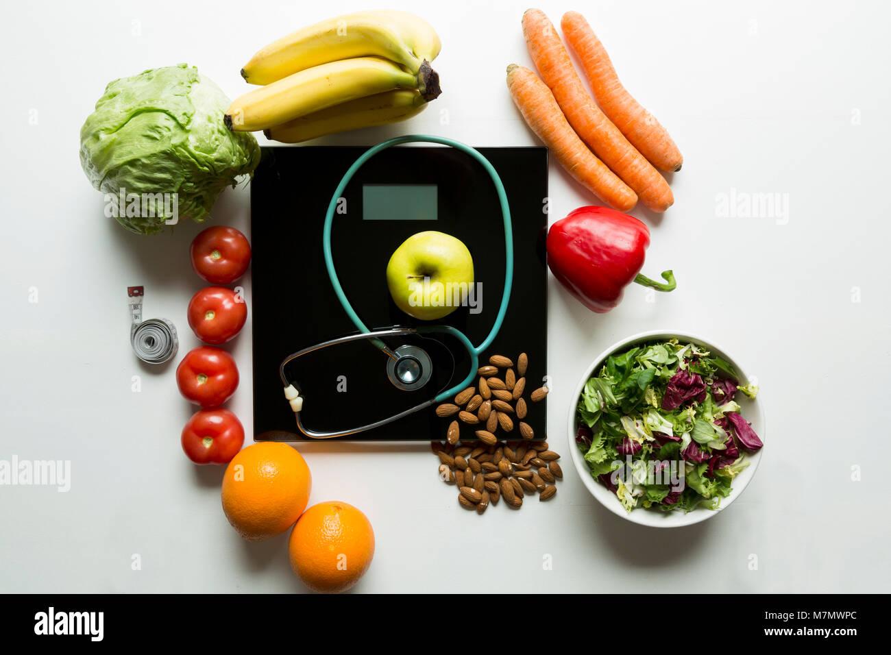 Gesundes Obst, Gemüse und Stethoskop auf Skalen. Gewicht Verlust und richtige Ernährung Konzept Stockbild