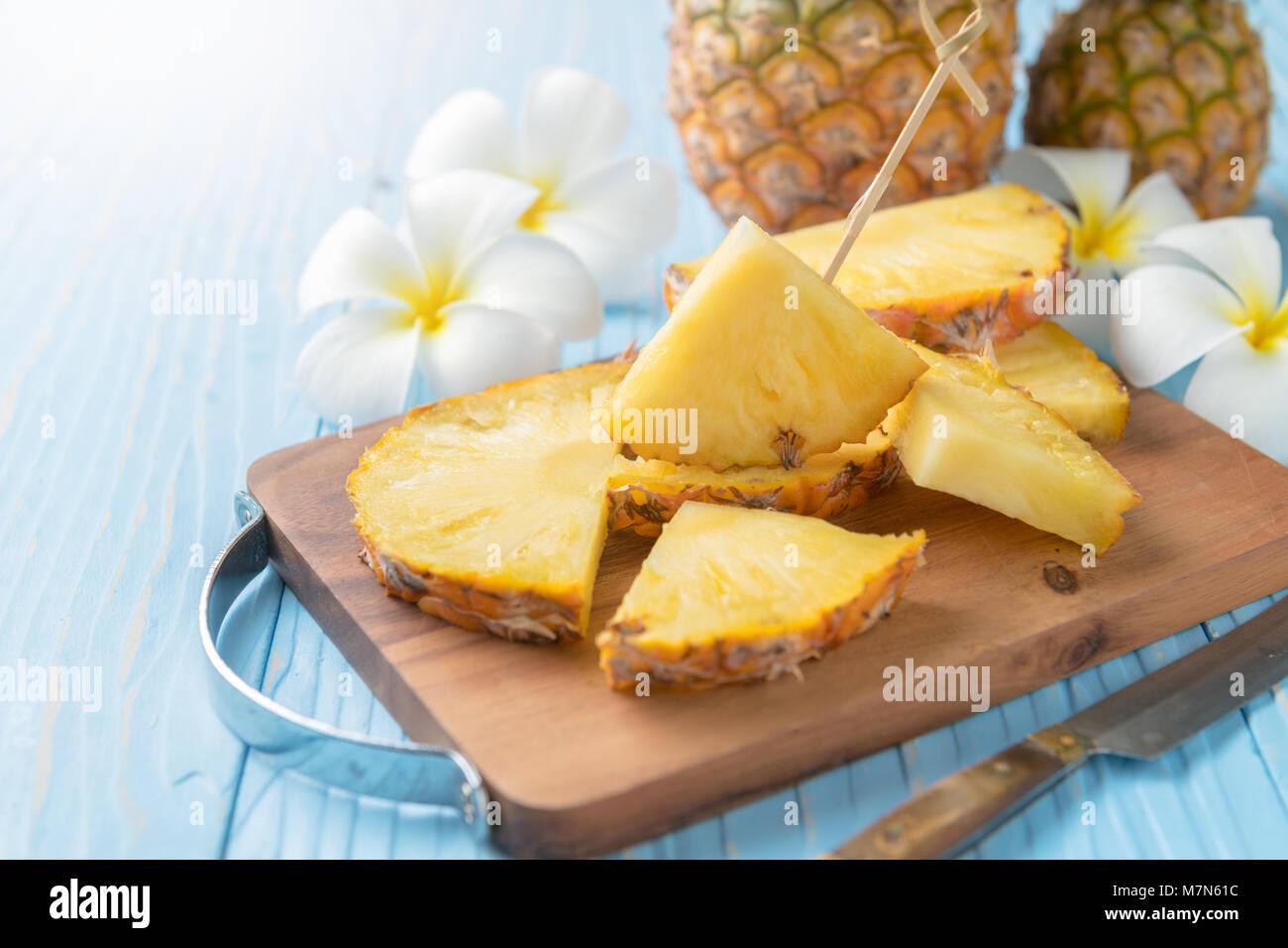 Frisch geschnittene Ananas auf Holz Block und blau Holz Hintergrund, Sommer Früchte Konzept Stockbild