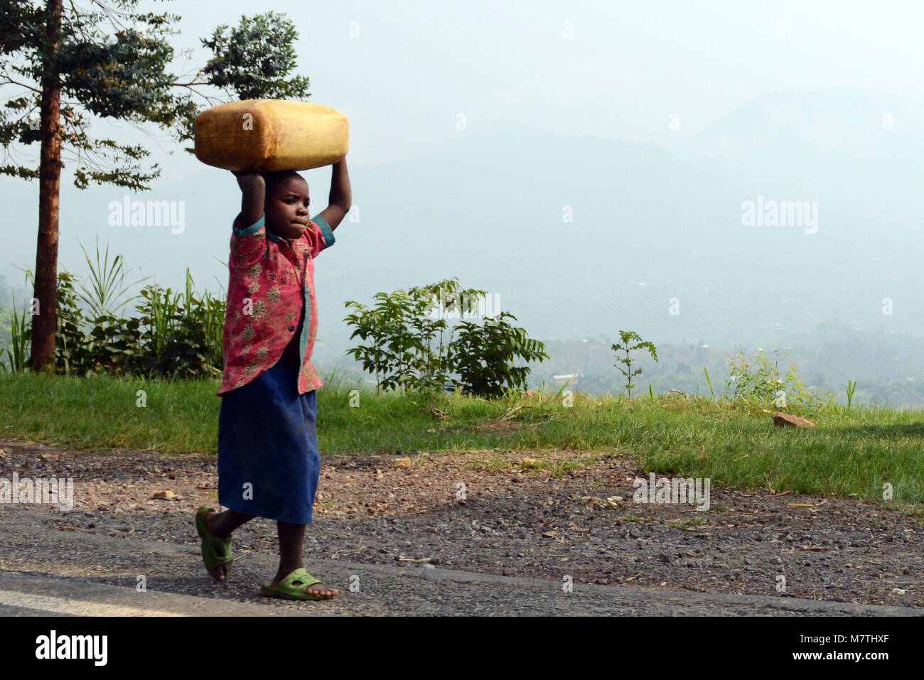 Ein Mädchen mit einem Kanister mit Wasser auf den Kopf. Stockbild