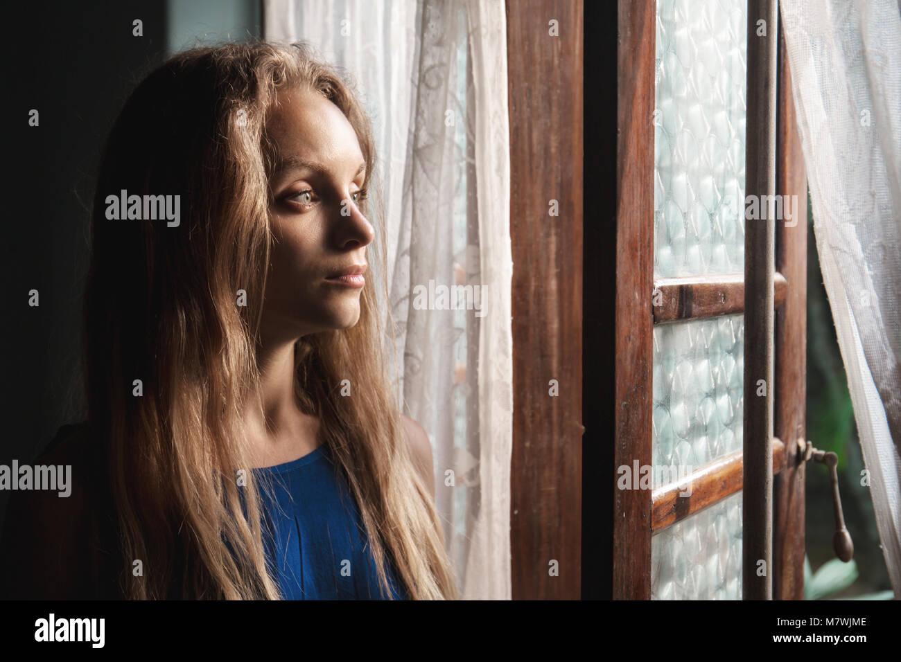 Die Frau in der Nähe eines Fensters Stockfoto