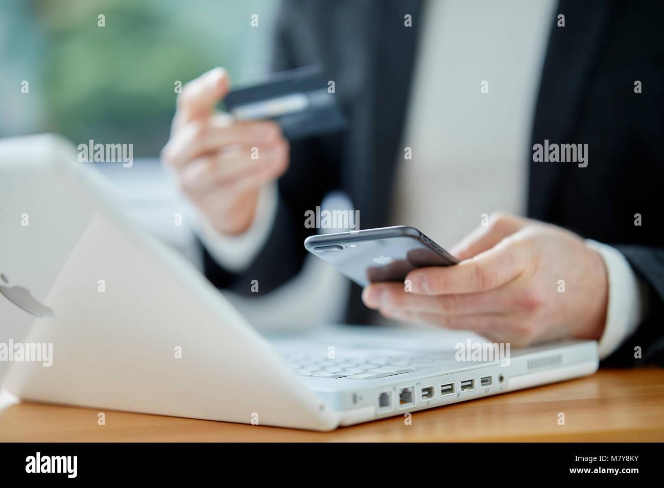 Mann mit Laptop holding Kreditkarte Stockbild