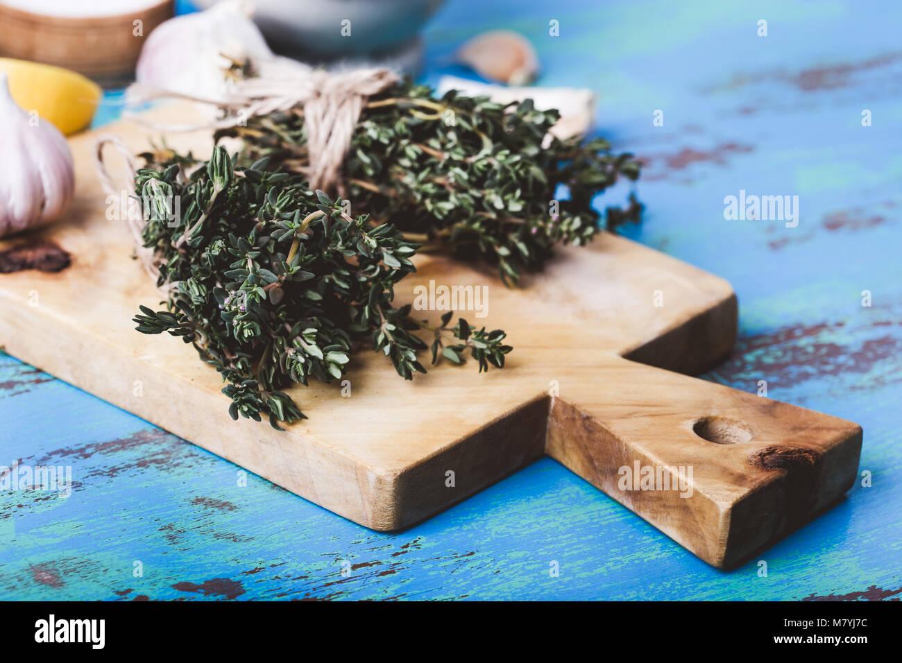 Bündel von Thymian, frischer Zitronen und Knoblauch auf Holz Schneidebrett. Zutaten der traditionellen mediterranen Stockbild